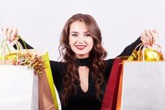 Μοντέρνη νέα γυναίκα brunette που κρατά τις ζωηρόχρωμες τσάντες αγορών στοκ φωτογραφία με δικαίωμα ελεύθερης χρήσης