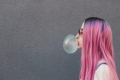 Μοντέρνη νέα γυναίκα hipster με τη μακριά ρόδινη τρίχα που φυσά μια φυσαλίδα με τη γόμμα φυσαλίδων στοκ εικόνα