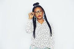 Μοντέρνη νέα μαύρη γυναίκα που στέκεται και σχετικά με τα προστατευτικά δίοπτρα Στοκ Εικόνα
