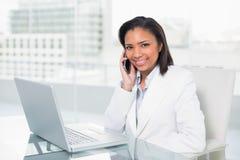 Μοντέρνη νέα μελαχροινή μαλλιαρή επιχειρηματίας που κάνει ένα τηλεφώνημα Στοκ Φωτογραφίες
