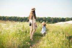 Μοντέρνη νέα μητέρα με το περπάτημα κοριτσιών μικρών παιδιών στοκ φωτογραφίες