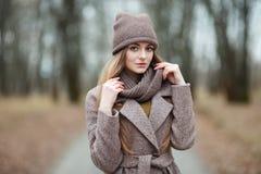 Μοντέρνη ξανθή γυναίκα στην καθιερώνουσα τη μόδα αστική outwear θέτοντας αλέα πάρκων κρύου καιρού δασική Εκλεκτής ποιότητας διαπο Στοκ Φωτογραφία