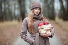 Μοντέρνη ξανθή γυναίκα στην καθιερώνουσα τη μόδα αστική outwear θέτοντας αλέα πάρκων κρύου καιρού δασική με τη συσκευασία των κόκ Στοκ Εικόνες