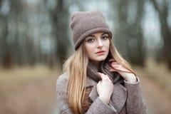 Μοντέρνη ξανθή γυναίκα στην καθιερώνουσα τη μόδα αστική outwear θέτοντας αλέα πάρκων κρύου καιρού δασική Εκλεκτής ποιότητας διαπο Στοκ Φωτογραφίες
