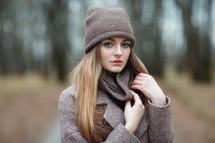 Μοντέρνη ξανθή γυναίκα στην καθιερώνουσα τη μόδα αστική outwear θέτοντας αλέα πάρκων κρύου καιρού δασική Εκλεκτής ποιότητας διαπο Στοκ φωτογραφία με δικαίωμα ελεύθερης χρήσης