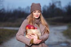 Μοντέρνη ξανθή γυναίκα στην καθιερώνουσα τη μόδα αστική outwear θέτοντας αλέα πάρκων κρύου καιρού δασική με τη συσκευασία των κόκ Στοκ Φωτογραφίες