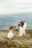 Μοντέρνη παράνυμφος και πανέμορφη νύφη που έχουν τη διασκέδαση και που πηδούν, BO Στοκ Εικόνες