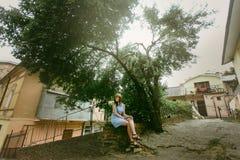 Μοντέρνη συνεδρίαση γυναικών hipster κάτω από τα όμορφα δέντρα σε ευρωπαϊκά στοκ εικόνες