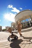 Μοντέρνη σύγχρονη μητέρα σε μια αστική οδό με ένα καροτσάκι. Νέο μ Στοκ Εικόνες