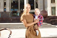 Μοντέρνη σύγχρονη μητέρα σε μια αστική οδό με ένα καροτσάκι. Νέο μ Στοκ εικόνες με δικαίωμα ελεύθερης χρήσης