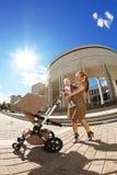 Μοντέρνη σύγχρονη μητέρα σε μια αστική οδό με το α Στοκ φωτογραφία με δικαίωμα ελεύθερης χρήσης