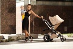 Μοντέρνη σύγχρονη μητέρα σε μια οδό πόλεων με ένα καροτσάκι. Νέο MO Στοκ φωτογραφία με δικαίωμα ελεύθερης χρήσης
