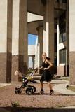 Μοντέρνη σύγχρονη μητέρα σε μια οδό πόλεων με ένα καροτσάκι Στοκ Εικόνες