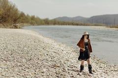 Μοντέρνη ταξιδιωτική γυναίκα boho στο καπέλο, poncho περιθωρίου και τον περίπατο μποτών Στοκ Φωτογραφίες