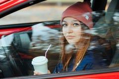 Μοντέρνη φίλαθλη γυναίκα brunette καθιερώνοντα τη μόδα αστικό σε outwear οδηγώντας ένα αυτοκίνητο με το μεγάλο άσπρο μίας χρήσης  Στοκ Φωτογραφίες