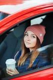 Μοντέρνη φίλαθλη γυναίκα brunette καθιερώνοντα τη μόδα αστικό σε outwear οδηγώντας ένα αυτοκίνητο με το μεγάλο άσπρο μίας χρήσης  Στοκ Εικόνα