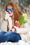 Μοντέρνη χαμογελώντας γυναίκα με τα μπλε γυαλιά ηλίου που εξετάζει την απόσταση καθμένος snowdrift στοκ εικόνα