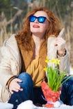 Μοντέρνη όμορφη γυναίκα που κοιτάζει κατά μέρος καθμένος στο χιονώδες έδαφος στοκ εικόνα
