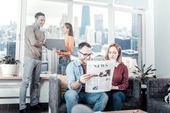 Μοντέρνοι ελκυστικοί συνεργάτες που κάθονται και που διαβάζουν την εφημερίδα Στοκ φωτογραφίες με δικαίωμα ελεύθερης χρήσης