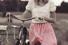 Μοντέρνοι ντυμένοι γύροι κοριτσιών σε ένα παλαιό ποδήλατο με μια αναδρομική επίδραση Στοκ Εικόνες