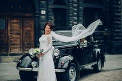 Μοντέρνοι νύφη και νεόνυμφος που θέτουν sensually κοντά στο αναδρομικό αυτοκίνητο με το boh Στοκ φωτογραφίες με δικαίωμα ελεύθερης χρήσης