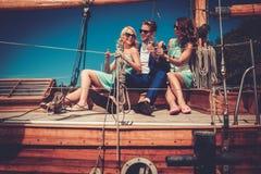 Μοντέρνοι πλούσιοι φίλοι που έχουν τη διασκέδαση σε ένα γιοτ πολυτέλειας Στοκ φωτογραφία με δικαίωμα ελεύθερης χρήσης
