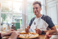 Μοντέρνος έφηβος που φορούν το μαχαίρι εκμετάλλευσης πετσετών και δίκρανο έτοιμο να φάει τη συνεδρίαση πιτσών ενάντια στο παράθυρ Στοκ φωτογραφίες με δικαίωμα ελεύθερης χρήσης