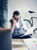 Μοντέρνος γενειοφόρος νεαρός άνδρας που φορά το άσπρο γιλέκο πουκάμισων γυαλιών που λειτουργεί το σύγχρονο ξεκίνημα εργασιακών χώ Στοκ Φωτογραφίες