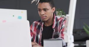 Μοντέρνος επιχειρηματίας που τρώει το μπισκότο εργαζόμενος στο lap-top στο γραφείο απόθεμα βίντεο