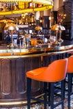 Μοντέρνος εσωτερικός φραγμός, στο εκλεκτής ποιότητας ύφος Πορτοκαλιοί καρέκλες, γυαλιά, λαμπτήρες και διακοσμήσεις σχεδιαστών στοκ φωτογραφία