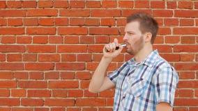 Μοντέρνος και μοντέρνος τύπος με μια γενειάδα που καπνίζει ένα vape ενάντια σε έναν τουβλότοιχο, διάστημα αντιγράφων, αργός-Mo, έ φιλμ μικρού μήκους