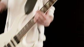 Μοντέρνος κιθαρίστας ρυθμού κινηματογραφήσεων σε πρώτο πλάνο με τα διαφορετικά μάτια στα άσπρα ενδύματα σε ένα μαύρο παιχνίδι υπο φιλμ μικρού μήκους