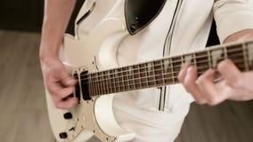 Μοντέρνος κιθαρίστας ρυθμού κινηματογραφήσεων σε πρώτο πλάνο με τα διαφορετικά μάτια στα άσπρα ενδύματα σε ένα μαύρο παιχνίδι υπο απόθεμα βίντεο
