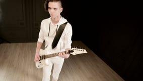Μοντέρνος κιθαρίστας ρυθμού με τα διαφορετικά μάτια στα άσπρα ενδύματα σε ένα μαύρο υπόβαθρο που παίζει εκφραστικά το λευκό απόθεμα βίντεο