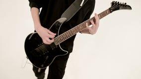 Μοντέρνος κιθαρίστας ρυθμού με τα διαφορετικά μάτια στα μαύρα ενδύματα σε ένα άσπρο υπόβαθρο που παίζει εκφραστικά το Μαύρο απόθεμα βίντεο