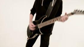 Μοντέρνος κιθαρίστας ρυθμού με τα διαφορετικά μάτια στα μαύρα ενδύματα σε ένα άσπρο υπόβαθρο που παίζει εκφραστικά το Μαύρο φιλμ μικρού μήκους