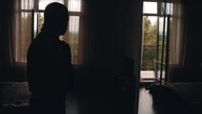Μοντέρνος νέος τύπος που δένει το δεσμό του που στέκεται μπροστά από το παράθυρο στο δωμάτιο και που κοιτάζει στον καθρέφτη Αυτό  απόθεμα βίντεο
