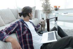 Μοντέρνος νεαρός άνδρας που κτυπά το κατοικίδιο ζώο του και που εργάζεται στο lap-top Στοκ Φωτογραφία