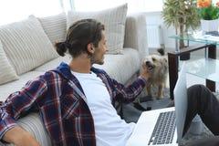 Μοντέρνος νεαρός άνδρας που κτυπά το κατοικίδιο ζώο του και που εργάζεται στο lap-top Στοκ Εικόνες