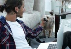 Μοντέρνος νεαρός άνδρας που κτυπά το κατοικίδιο ζώο του και που εργάζεται στο lap-top Στοκ εικόνες με δικαίωμα ελεύθερης χρήσης