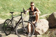 Μοντέρνος νεαρός άνδρας με μια συνεδρίαση ποδηλάτων σε έναν βράχο Μαύρη μπλούζα W Στοκ Εικόνα
