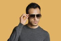 Μοντέρνος νεαρός άνδρας που φορά τα γυαλιά ηλίου πέρα από το χρωματισμένο υπόβαθρο Στοκ εικόνες με δικαίωμα ελεύθερης χρήσης