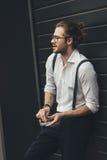 Μοντέρνος νεαρός άνδρας στα θεάματα που κρατά ashtray καπνίζοντας και κοιτάζοντας μακριά Στοκ εικόνες με δικαίωμα ελεύθερης χρήσης