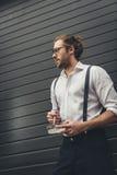 Μοντέρνος νεαρός άνδρας στα θεάματα που κρατούν ashtray και που καπνίζουν το τσιγάρο Στοκ Εικόνες