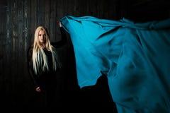 Μοντέρνος ξανθός σε ένα σκοτεινό υπόβαθρο με το φωτεινό πετώντας ύφασμα, χρωματίζει το μπλε Στοκ Φωτογραφίες