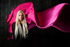 Μοντέρνος ξανθός σε ένα σκοτεινό υπόβαθρο με το φωτεινό πετώντας ύφασμα, χρωματίζει το ροζ Στοκ εικόνα με δικαίωμα ελεύθερης χρήσης