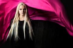 Μοντέρνος ξανθός σε ένα σκοτεινό υπόβαθρο με το φωτεινό πετώντας ύφασμα, χρωματίζει το ροζ Στοκ φωτογραφίες με δικαίωμα ελεύθερης χρήσης