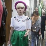 Μοντέρνος ξανθός στην άσπρη εκλεκτής ποιότητας μπλούζα, την πράσινα φούστα και burgundy το καπέλο είναι στο δρόμο της Κολούμπια Στοκ Εικόνα