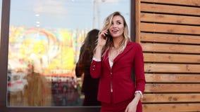 Μοντέρνος ξανθός στο κόκκινο έξυπνο κοστούμι που χρησιμοποιεί το τηλέφωνο και το μήνυμα απόθεμα βίντεο