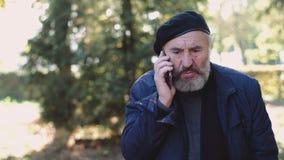 Μοντέρνος πρεσβύτερος στο καπέλο που μιλά στο τηλέφωνο συναισθηματικά στην ηλιόλουστη οδό φιλμ μικρού μήκους